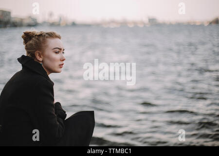 Side view of thoughtful young woman wearing black coat looking away by river in city - Stock Photo