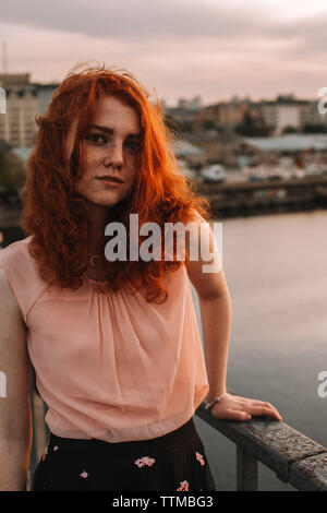 Portrait of young woman with red hair standing by railing on bridge - Stock Photo