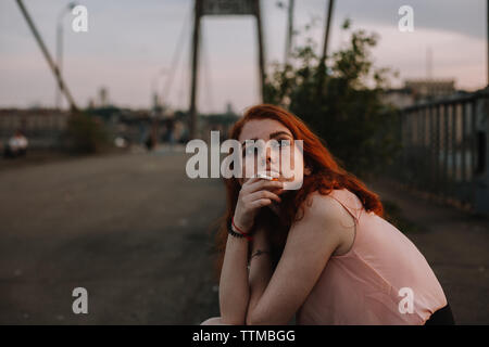 Teenage girl with freckles smoking cigarette while sitting on bridge - Stock Photo