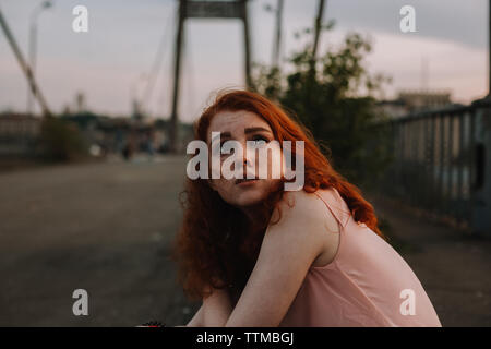 Portrait of teenage girl with freckles sitting on bridge in city - Stock Photo