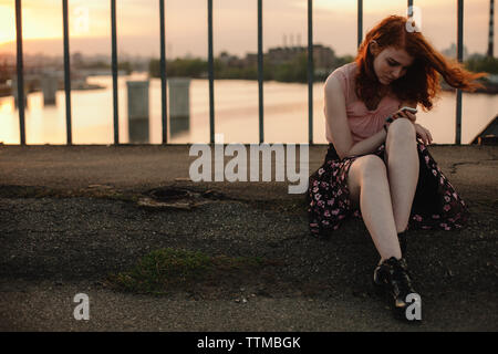 Young redhead woman using smart phone while sitting on bridge in city Stock Photo