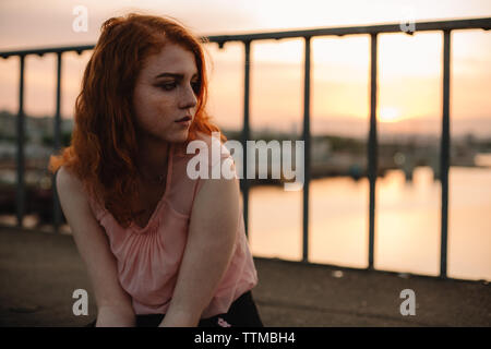 Portrait of teenage girl with freckles sitting on bridge at sunset - Stock Photo
