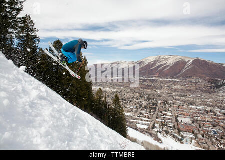 USA, Colorado, Aspen, skier getting air on a trail called Corkscrew with the town of Aspen in the distance, Aspen Ski Resort, Ajax mountain - Stock Photo