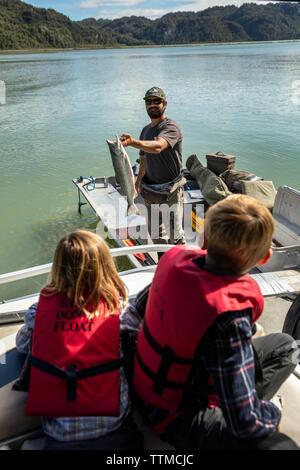 USA, Alaska, Redoubt Bay, Big River Lake, a fisherman showing off his catch - Stock Photo