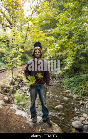 USA, Oregon, Ashland, portrait of Carston Peer in Lithia park holding flowers and leaves that he has collected and woven into a wreath - Stock Photo