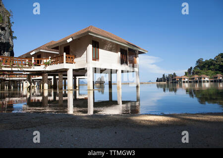 PHILIPPINES, Palawan, El Nido, Lagen Island Resort cottages sit over the water and below the rocky cliffs in Bacuit Bay in the South China Sea - Stock Photo