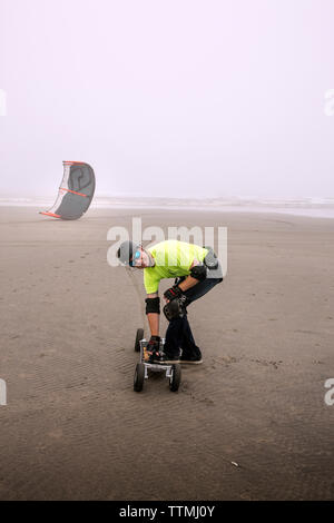 USA, Washington State, Long Beach Peninsula, International Kite Festival, power beach kite boarding in the fog - Stock Photo