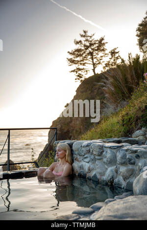 USA, California, Big Sur, Esalen, a woman sits in the Baths and takes in the evening view, the Esalen Institute - Stock Photo