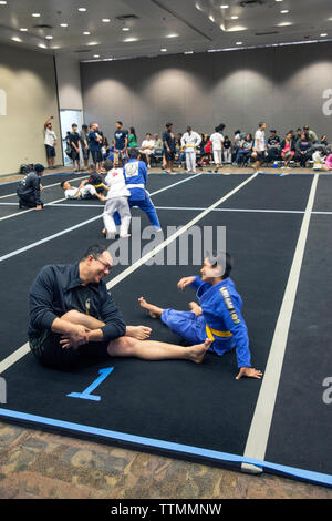 USA, Oahu, Hawaii, Jujitsu Martial Arts fighter Keith Chang and his nephew streatch before they grapple at the ICON grappling tournament in Honolulu - Stock Photo