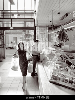 FRANCE, Burgundy, woman shopping at the local butcher, Dijon (B&W) - Stock Photo
