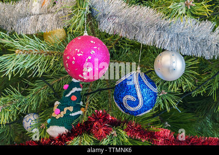 Fragment of beautifully decorated tinsel, toys and garlands of the Christmas fir tree - Stock Photo