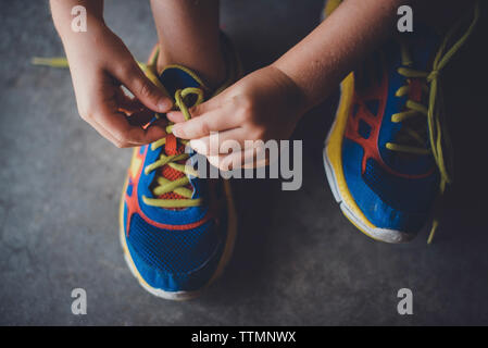 Cropped hands of boy tying shoelace - Stock Photo
