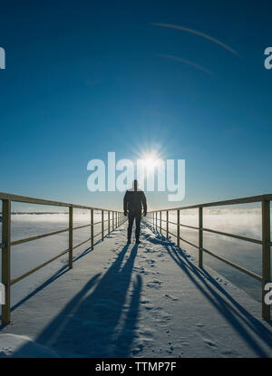 Rear view of man standing on snow covered pier over frozen lake against sky - Stock Photo