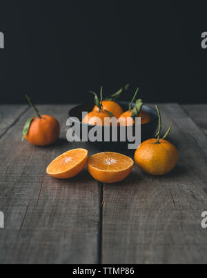 Oranges in bowl on wooden table against black background - Stock Photo
