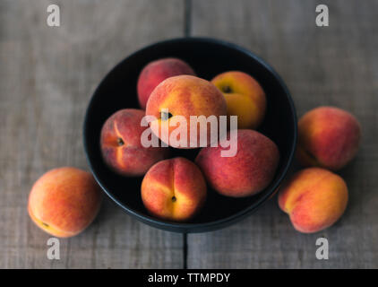 High angle view of peaches in bowl on wooden table - Stock Photo