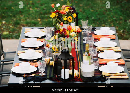 Flower vases with crockery arranged on dining table in backyard - Stock Photo