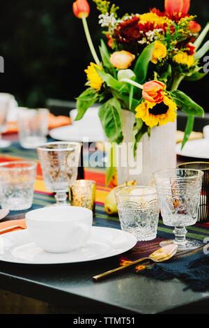 Flower vase with crockery arranged on table in backyard - Stock Photo