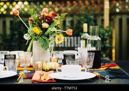 Flower vase with place setting and wine bottles on dining table in backyard - Stock Photo