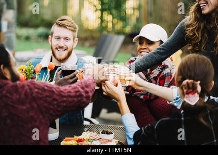 Happy friends toasting drinks while sitting in backyard - Stock Photo