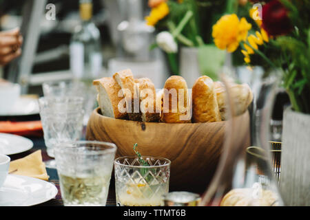 Breads in wooden bowl with drinks served on table - Stock Photo