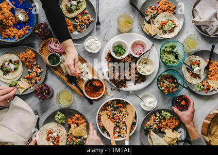 Cropped hands of friends having food at table during social gathering - Stock Photo