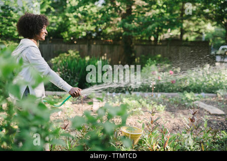 Side view of mature woman watering plants in garden - Stock Photo
