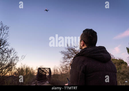 Man Flying drone against sky during sunset - Stock Photo