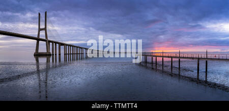 Vasco da Gama Bridge over Tagus River against cloudy sky during sunset - Stock Photo