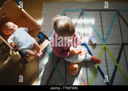A baby girl sitting on carpet playing with her dolls