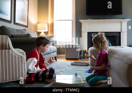 Siblings playing board game at home - Stock Photo