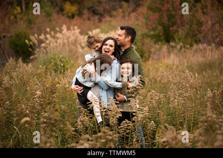 Parents enjoying with daughters while standing amidst plants against trees in forest - Stock Photo