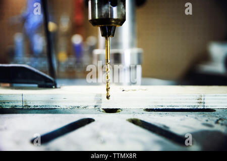 Close-up of drill bit over wood at workshop - Stock Photo