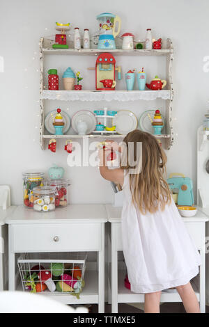 Rear view of girl holding teapot while playing in playhouse - Stock Photo