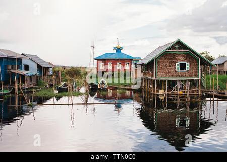 Stilt houses by Inle lake against sky - Stock Photo