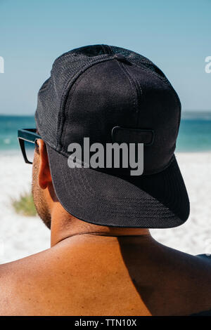 Rear view of shirtless man wearing cap looking at sea while sitting on Hyams Beach against clear blue sky during sunny day - Stock Photo