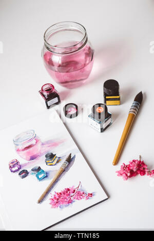 High angle view of watercolor paints with painting on table - Stock Photo