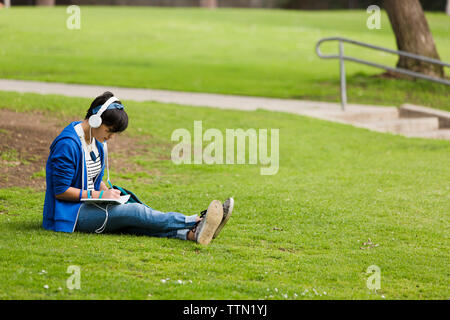 Full length of teenage girl listening music while writing on journal at park - Stock Photo