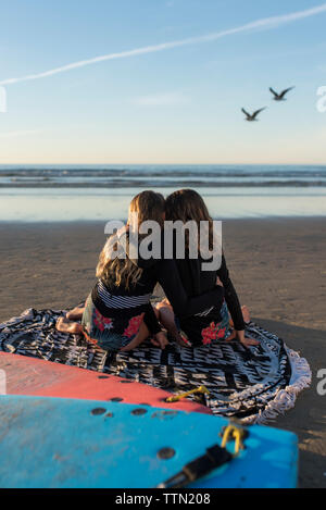 twin sisters hugging while sitting on the beach watching the surf - Stock Photo