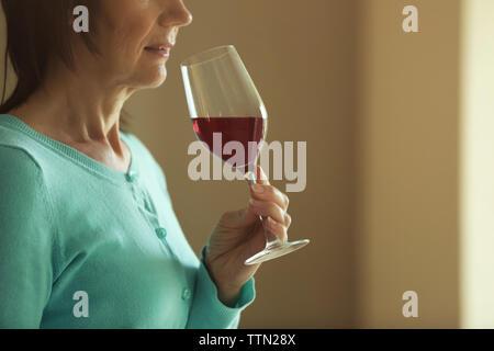 Woman tasting red wine - Stock Photo