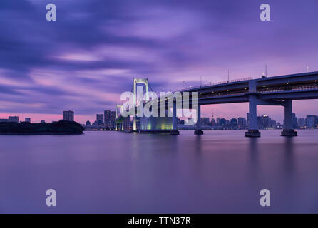 Rainbow bridge over river with Tokyo tower and sky during sunset - Stock Photo