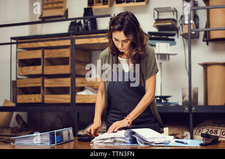 Mature female owner doing paperwork at coffee shop - Stock Photo