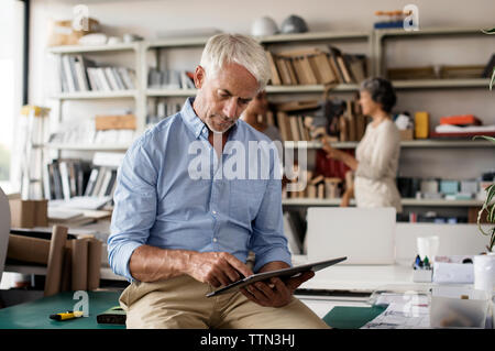 Male interior designer using tablet computer while female colleagues discussing in background - Stock Photo