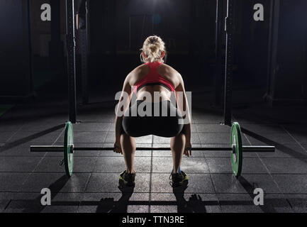 Rear view of woman picking barbell at gym - Stock Photo