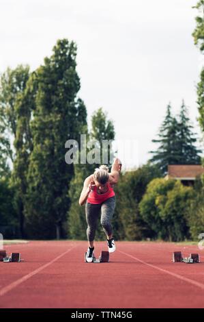 Athlete running from starting block on track - Stock Photo