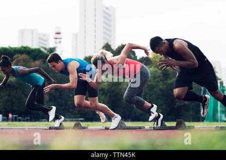 Athletes running from starting blocks on track - Stock Photo