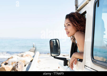 Woman peeking through car window at beach during sunny day - Stock Photo