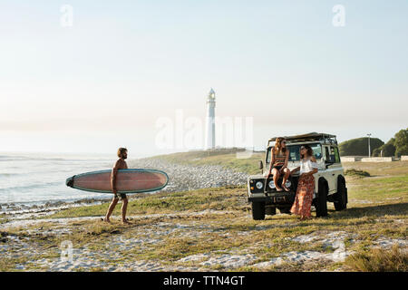 Man with surfboard walking towards female friends at beach against clear sky - Stock Photo