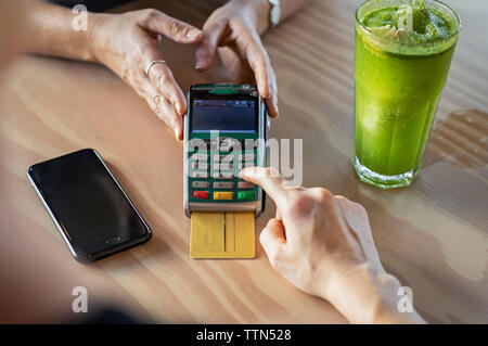 Cropped hands of female customer making credit card payment to owner on wooden table in cafeteria - Stock Photo