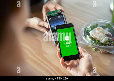 Cropped hands of female customer making mobile payment to owner on wooden table in cafeteria - Stock Photo