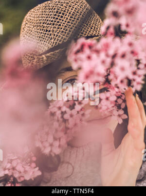 Close-up portrait of young woman with cherry blossoms wearing hat at park - Stock Photo